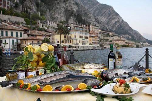 gastronomia, tavola imbandita con prodotti tipici del Garda, pesce, limoni, presso l'albergo ristorante Gemma, sullo sfondo il il porticciolo e il paese di Limone del Garda, Lombardia